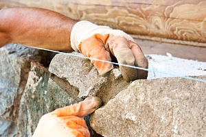 a worker doing masonry restoration for stone walls