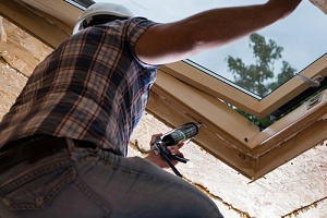 man performing interior caulking on a big window