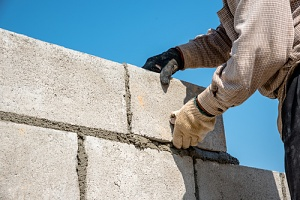 worker doing masonry repair services to a stone wall