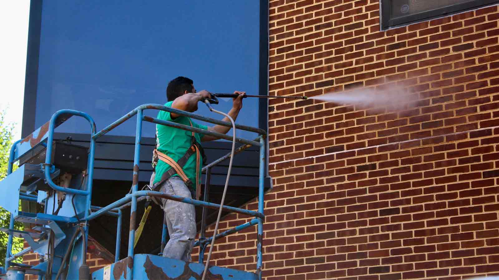 Man powerwashing building