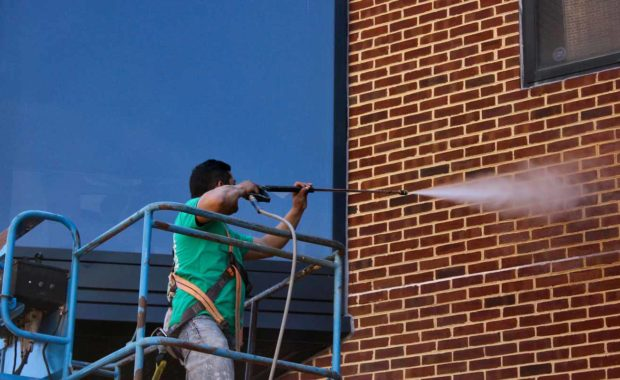 Waterproof caulking employee powerwashing exterior of Penny Hall