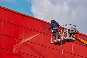 Man performing a washing service on a commercial building