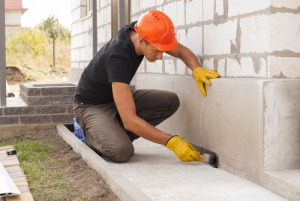 Man repairing leaks and cracks with cementitious waterproof caulking
