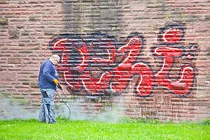 commercial pressure washer removing graffiti on building