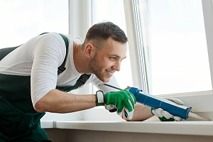 Caulking contractor working on a window