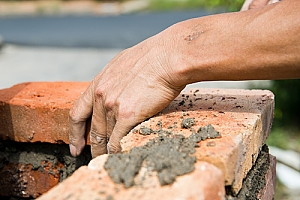 Hand removing old brick