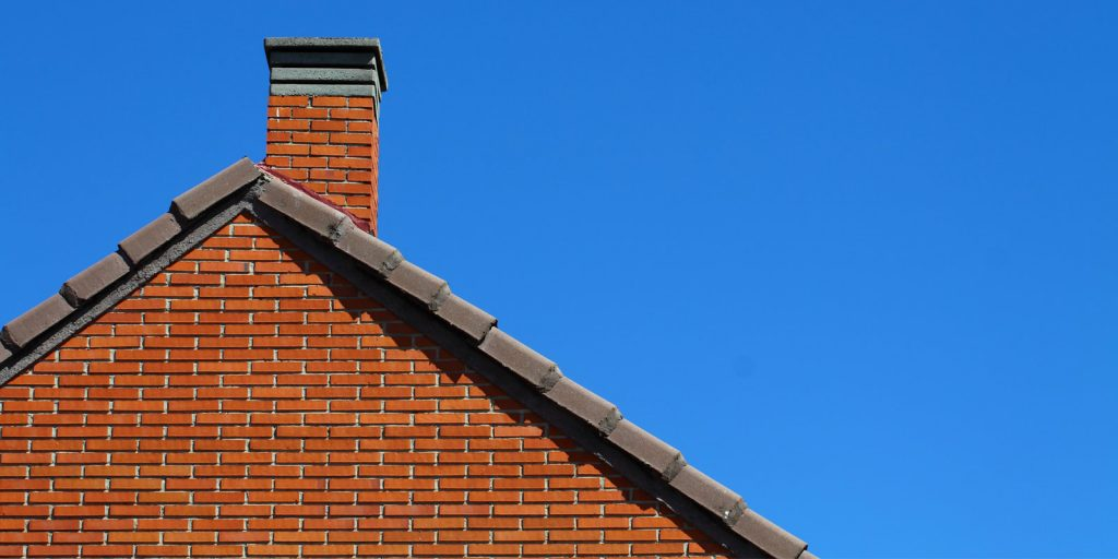 Chimney on roof in blue sky