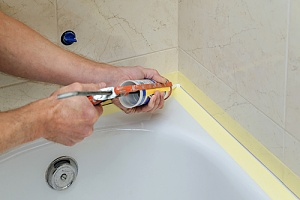 Person applying waterproof caulk