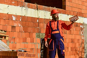 Masonry repair man holding brick