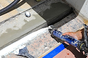 commercial caulking taking place on the roof of a building