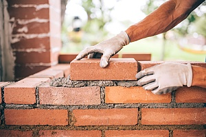 Masonry repair man laying bricks