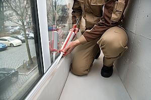 Worker waterproof caulking a window
