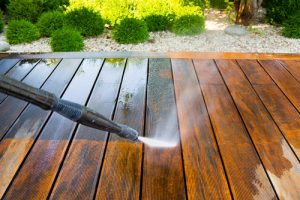 A power washer power washing a wooden surface