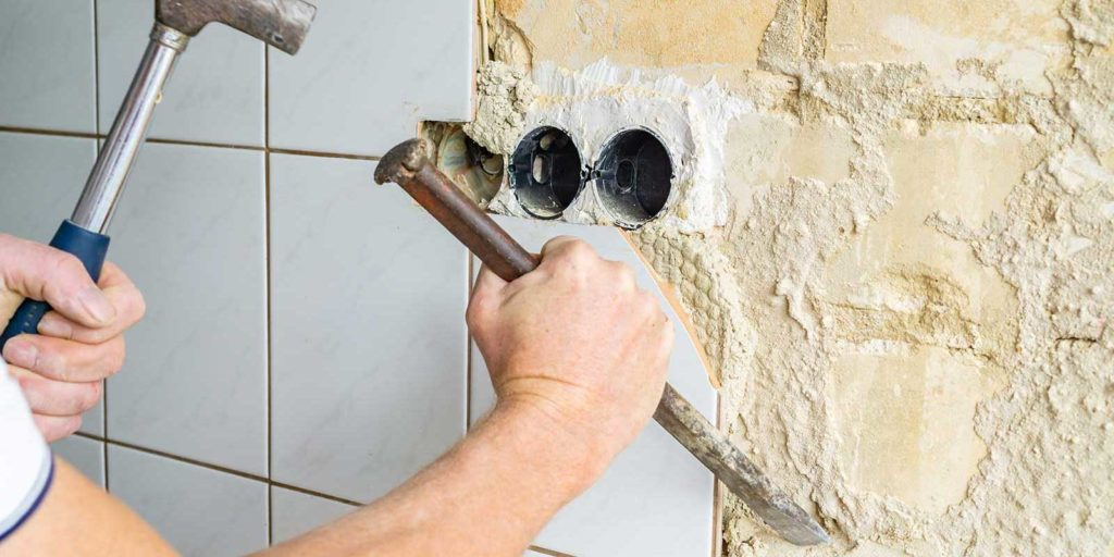 Commercial waterproofing contractor removing tile from a wall