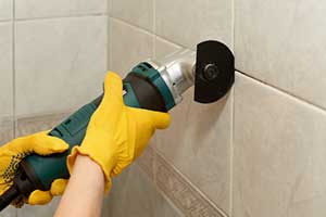 Contractor chiseling at grout around tile