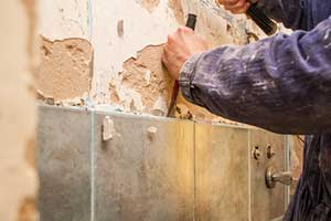 Man removing tile after reading article on how to remove tile
