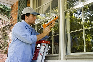 a contractor applying exterior caulking to a residence