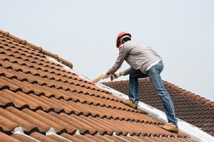 a contractor caulking a roof to prevent water damage to a residence