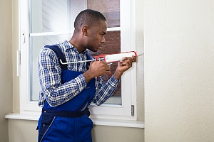 a contractor caulking the outside of a residential window pane