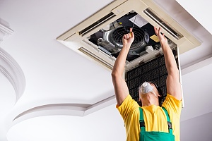 employee repairing a broken air conditioning during summer
