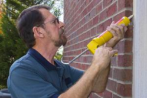 A person applying caulk on the exterior of his home