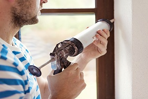 man caulking between window and building of a home
