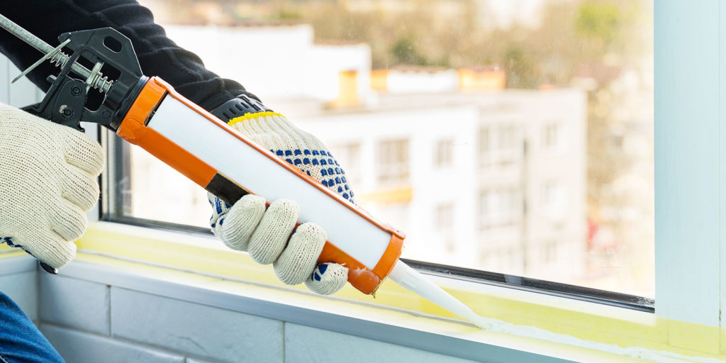 waterproof caulking a window with gloves on