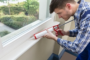 a man doing one type of waterproofing on a window