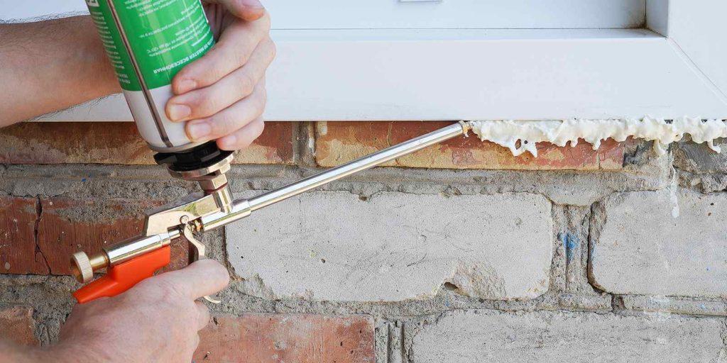 A handyman using polyurethane caulk for installing a plastic window