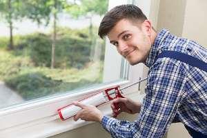 A male worker caulking Interior Windows