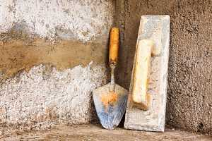 Masonry restoration tools leaning on a rough concrete wall