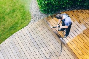 a man powerwashing a deck and making it clean