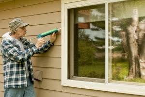 man being hired to work on window caulking on a home