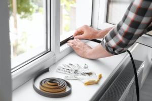 man working to do window caulking to fix leaks
