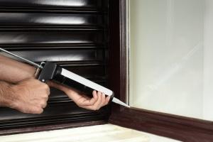 applying interior caulking to the home wall