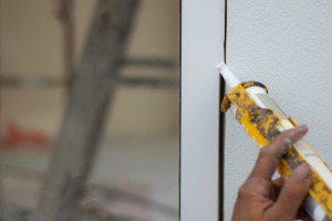 window caulking being done on a window to keep out water