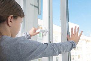 A little girl opening double glaze window