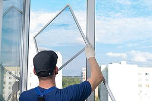 Worker installing Window. This is also refer to as window glazing