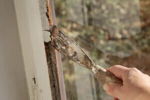 Man Taking out Window glazing with Tool
