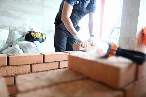 male builder hand in gloves holding clay brick working on a Masonry Repair Service
