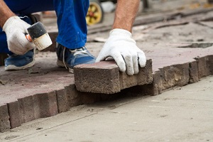professional workers laying paving slabs for a Masonry Repair Service