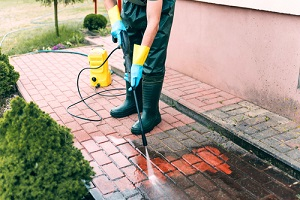 man cleaning red conrete pavement block using Commercial Pressure Washing