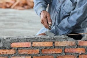 worker building wall with cament and brick on a masonry repair