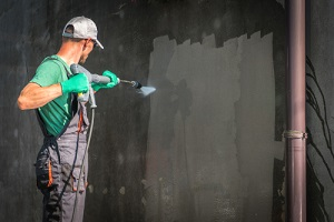 building elevation Commercial Pressure Washing Services by worker with power washer