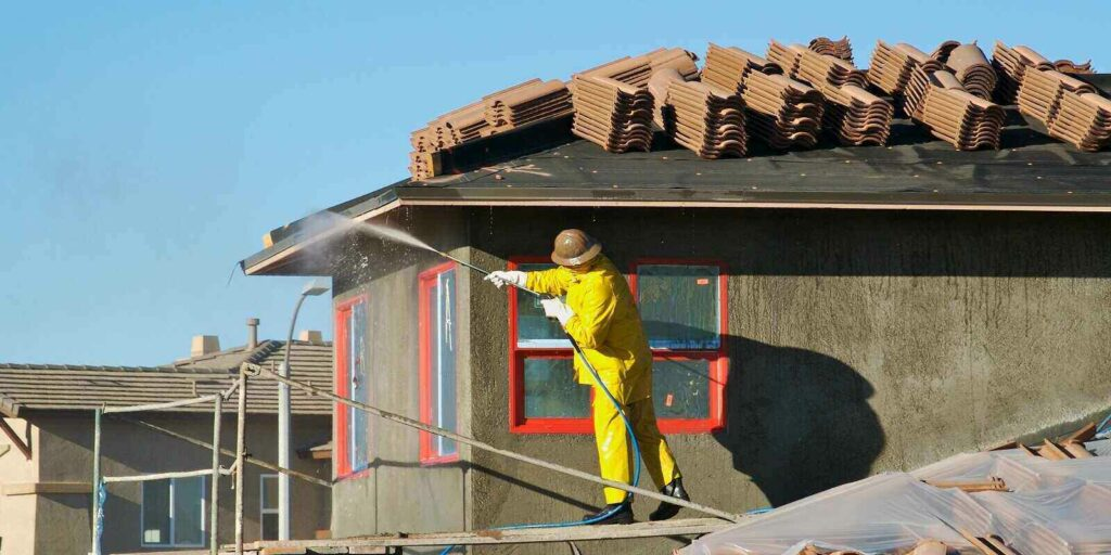 construction worker pressure washes fresh applied surface of new home exterior