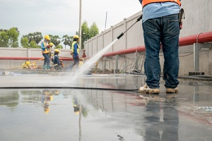 construction worker concrete floor cleaning with high Pressure Wash water jet