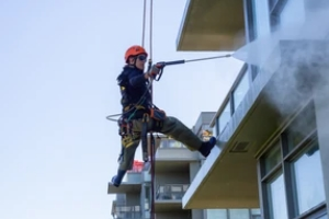 man powerwashing a building glass for Pressure Washing Services