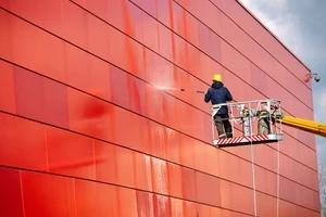 man Pressure Wash a big red building