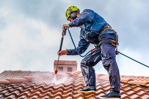 worker Pressure Washing Services on the roof with pressurized water