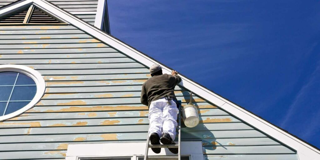 contractor or painter on a ladder doing exterior paint work